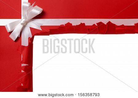 Christmas Gift Torn Open, White Ribbon Bow, Red Wrapping Paper Background, Copy Space