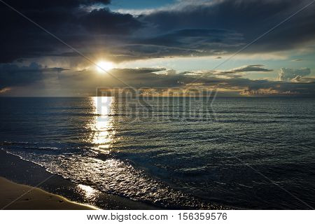 Reflection On Sea At Sunset Over Dynamic Sky