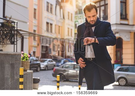 Hurry to work. Businessman is going in city and looking at watch with concentration