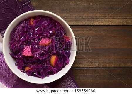 Braised red cabbage with apple in bowl photographed overhead on dark wood with natural light (Selective Focus Focus on the top of the dish)
