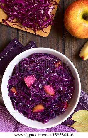 Braised red cabbage with apple in bowl surrounded by ingredients photographed overhead on dark wood with natural light (Selective Focus Focus on the top of the dish)