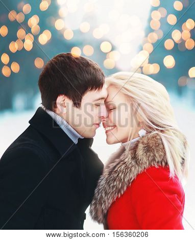 Christmas romantic sensual couple in love to cold winter day over celebration bokeh gentle kiss moment