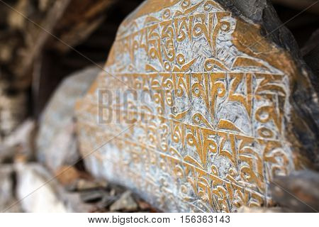 Malang, Nepal - May 6, 2016: Mani stones in Nepalese village, ancient buddhist carved stones with sacred religious mantras written in Tibetan language