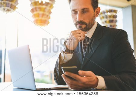 Smart businessman is looking at his mobile phone with seriousness. He is sitting at table near laptop in restaurant