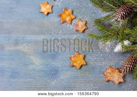 Star shaped ginger cookies and spruce branches with cones on blue wooden background with text space. Christmas and new year concept.