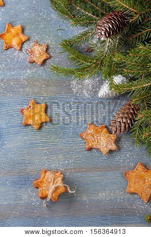 Star shaped ginger cookies and spruce branches with cones on blue wooden background. Christmas and new year concept.