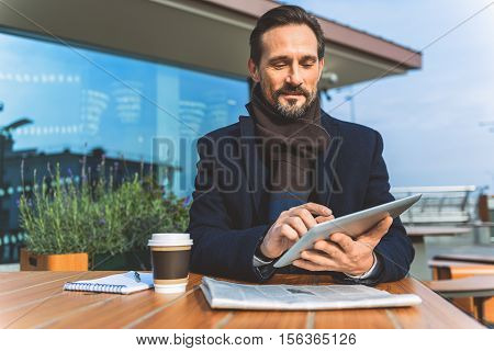 Joyful businessman is using tablet on coffee break. He is sitting at table in cafeteria outdoors and smiling