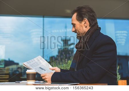 Joyful senior man is interested in news. He is looking at paper and smiling. Man is sitting at table near cup of coffee and tablet in restaurant outdoors