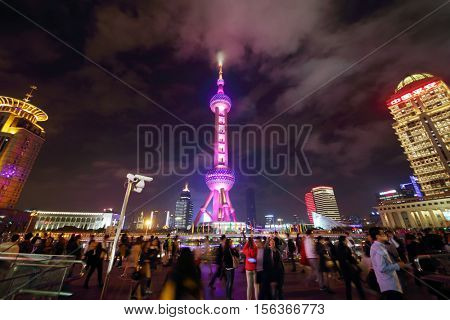 SHANGHAI, CHINA - NOV 6, 2015: TV tower Oriental Pearl and tourists at night, This tower is third highest in Asia