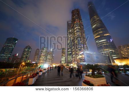 SHANGHAI, CHINA - NOV 6, 2015: Beautiful tall skyscrapers and people at night, China tallest skyscraper (Shanghai Tower) height of 630 meters