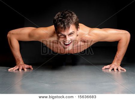 young male doing physical exersize on a dark background