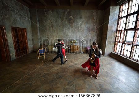 MOSCOW - FEB 9, 2016: Woman in dress and man in hat dance tango and girl plays sax (models with relases) Cross Photo studio - Amber Hall