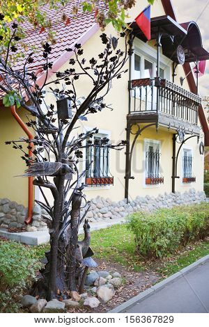 MOSCOW - SEP 22, 2015: Beautiful tree made of iron and birdhouses and birds near cottage in VDNH