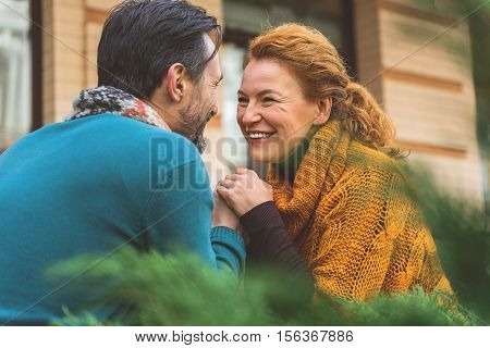 Joyful middle-aged loving couple is holding hands and smiling. They are sitting outdoors