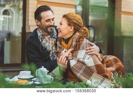 Joyful senior man and woman are sitting in cafe outside and hugging. They are looking at each other with love and laughing. Lady is warming up by blanket