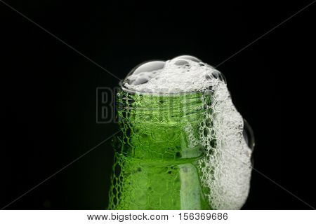 Green beer bottle neck with foam on black background