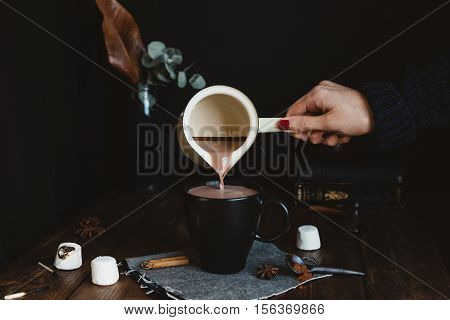 Female Pouring Hot Chocolate Drink Into A Black Mug on Rustic Wooden Table
