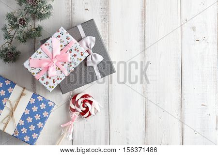 Christmas gift boxes and lollypop under fur tree branch on white wooden background