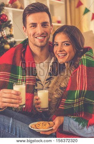 Happy young couple holding glasses of milk cookies and smiling while celebrating Christmas at home