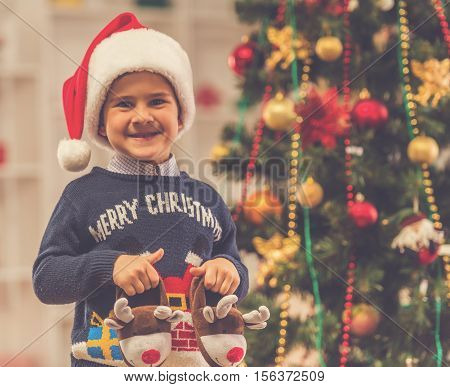 Happy little boy in Santa's hat is looking at camera and smiling while celebrating Christmas at home
