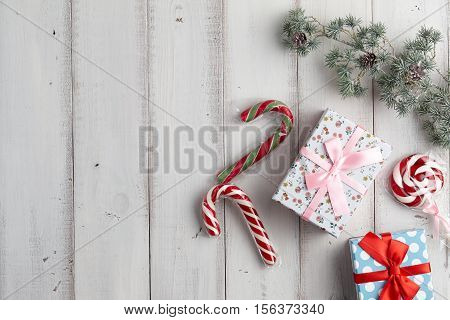 Christmas gift boxes with lollypop and candy canes under fur tree branch on white wooden background