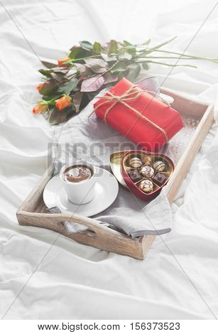 Romantic breakfast with coffee chocolate pralines gift box and pretty bouquet of roses valentine's day or holiday concept