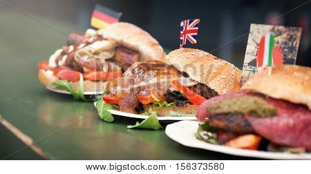 Various arts of burgers from different countries on a counter street food or unhealthy food concept selective focus