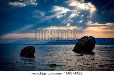 dark stones in sea water before thunderstorm