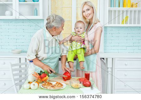 Mom with a child in the kitchen and near grandmother prepares vegetarian dinner.