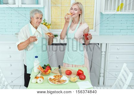 Girl and grandmother eat pizza they cooked in the kitchen.