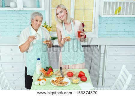 Young girl and her mother preparing food in the kitchen.