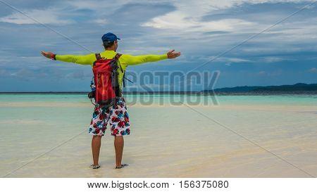 Happy Traveler on White Sand Bank during Low Tide, Kri Island. Raja Ampat, Indonesia, West Papua.