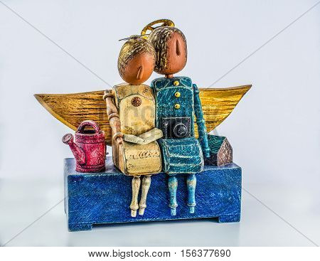 The sculptural composition of the tree two dolls: he and she. Couple in love on vacation. In a primitive style.