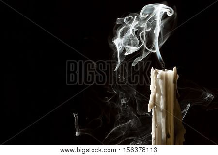 Candle blow off with smoke on black background