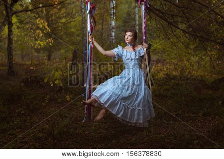 Girl swinging on a swing in the woods her vintage retro dress.