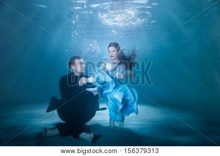 Man and woman on the bottom of the pool spend the tea ceremony.