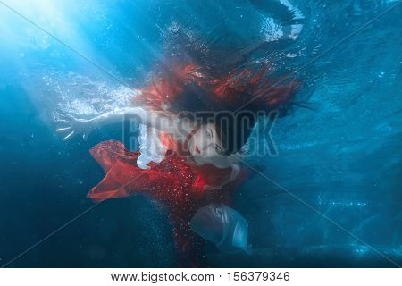 Girl in red dress under water it is a mermaid.
