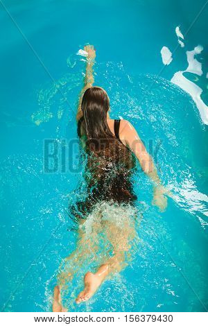 Woman resting at swimming pool. Young girl wearing black dress floating. Water aerobics fitness.