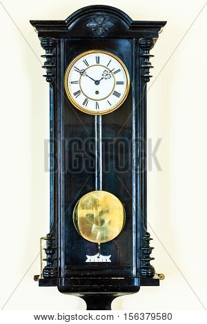 old big wooden pendulum clock hanging on wall