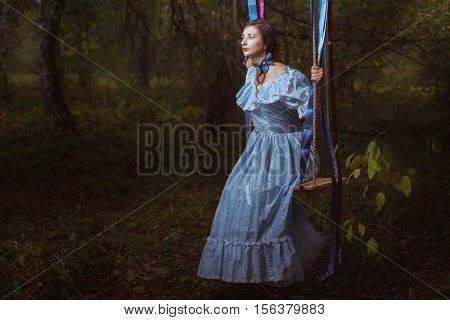 Young girl in fairy forest on the swing she retro vintage dress.