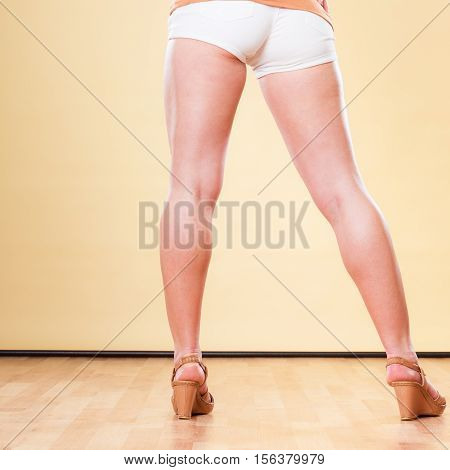 Female legs in summer shorts and fashionable shoes part of body back view