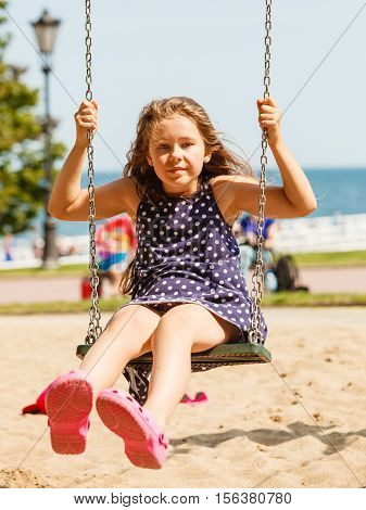 Have fun and leisure concept. Long haired enjoyable girl swinging outdoor in garden playground. Lovely child playing on swing-set.