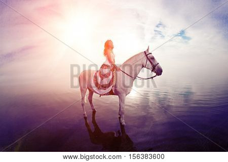 Young woman on a horse. Horseback rider, woman riding horse on beach.