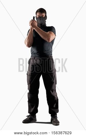 man in black uniform and headgear with gun in prepared position isolated on white background