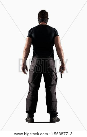 man in black uniform and headgear with gun isolated on white background, rear view