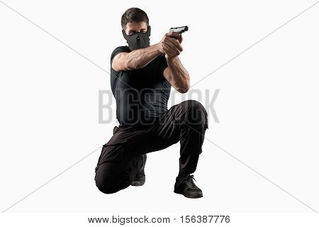 man in black uniform and headgear with gun in shooting position isolated on white background