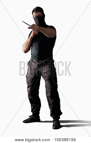 Man in black uniform with knife in combat stance isolated on white