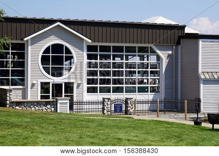 HARBOR SPRINGS, MICHIGAN / UNITED STATES - AUGUST 3, 2016: The Boathouse Club, in the Walstrom Marine boathouse, is next to the Zorn Park Public Beach near downtown Harbor Springs.