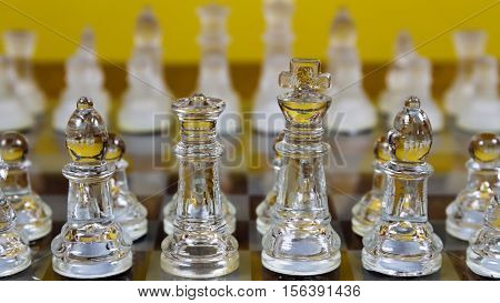 Glass Chess Pieces Setup On Board With Focus On Near Side