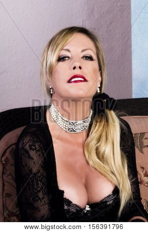 Older Blond Woman Sitting In Black lace Lingerie With Necklace And Cleavage